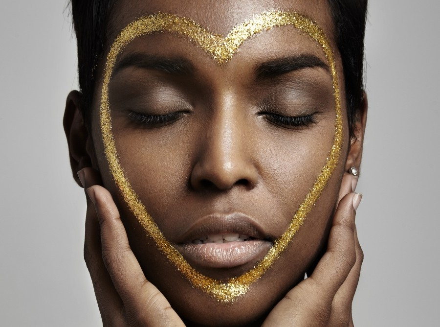 black woman with a golden heart on her face